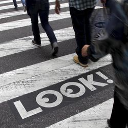 """Pedestrians walk past a """"Look!"""" sign on the crosswalk at the intersection of 42nd St. and 2nd Ave. in New York, Thursday, Sept. 20, 2012.  Crossing the street in New York City is complicated: Even when it's one-way, you should look both ways, and stop texting for a few seconds.  That's what city transportation officials tell pedestrians who often miss getting hit in the chaotic every-which-way-including-loose mill of vehicles, bicycles, scooters and sometimes, carriage horses.  They're making their point visible with """"LOOK!"""" signs stenciled at 110 of the most dangerous intersections in the city's five boroughs."""