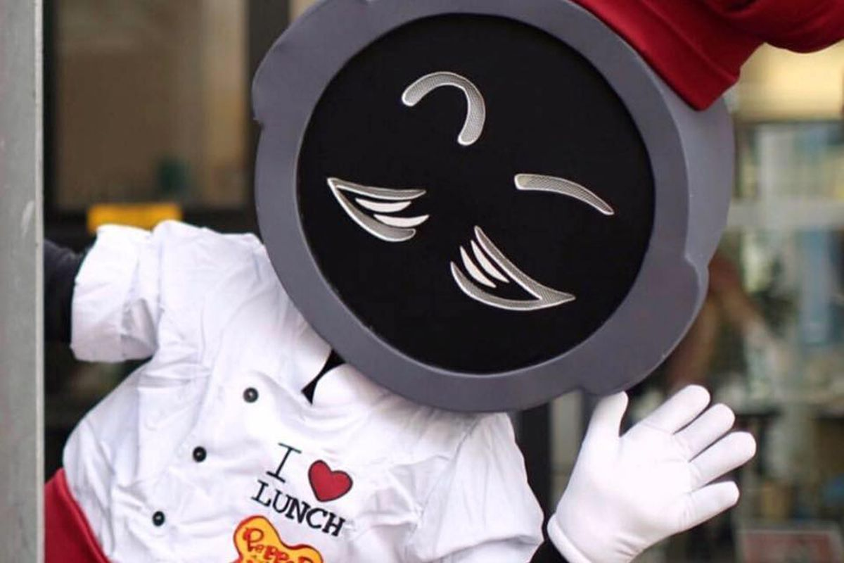 The Pepper Lunch mascot, with a face modeled after the popular chain's signature cast iron skillet, waves at the camera.