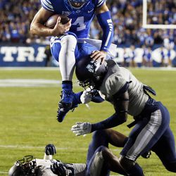 Taysom Hill (4) of the Brigham Young University Cougars flies into the end zone for a touchdown against Utah State during NCAA football in Provo, Friday, Oct. 3, 2014. At right is Daniel Gray (1) of the Utah State Aggies.