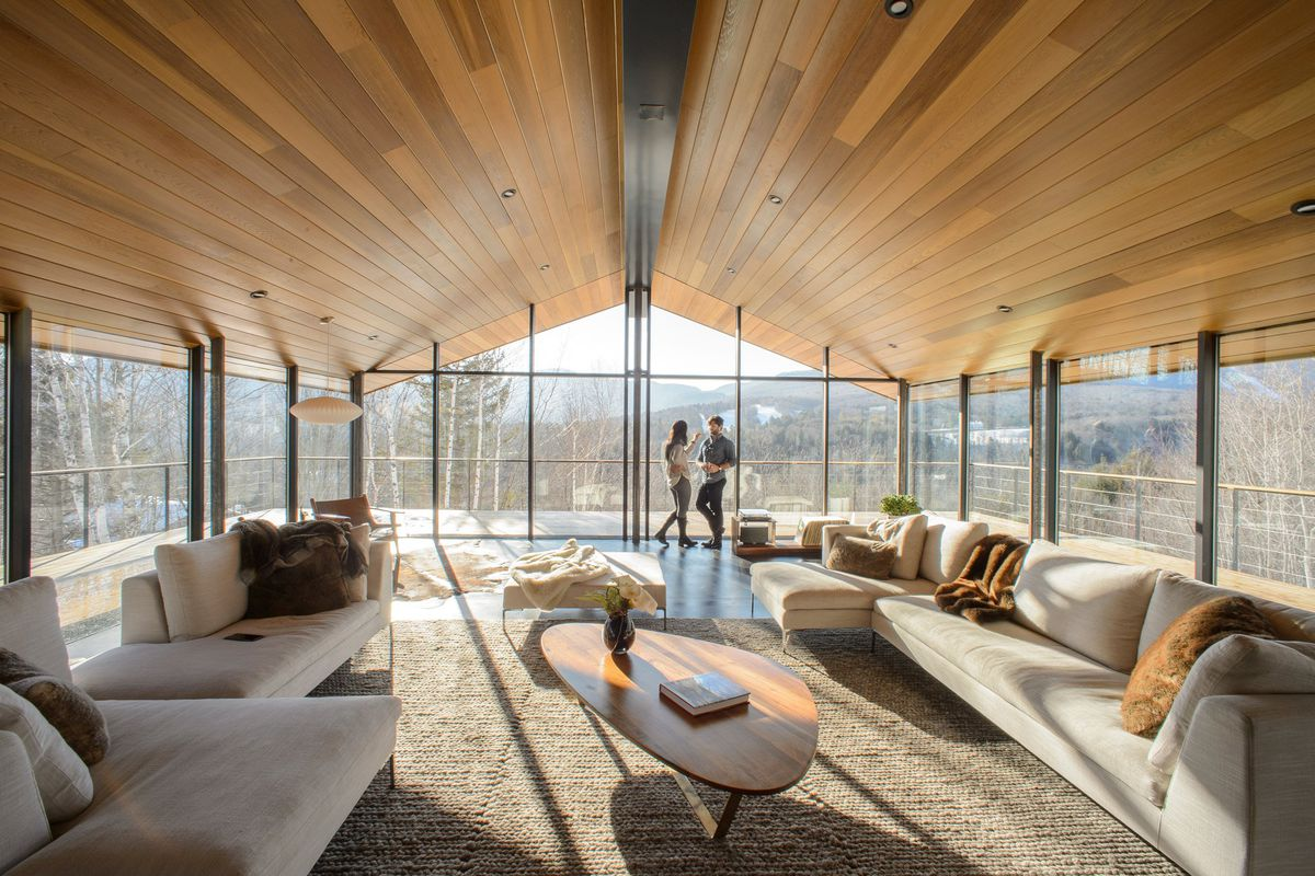 Interior shot of living room with cathedral ceiling clad in wood paneling, and glass walls on three sides looking out onto nature landscape.