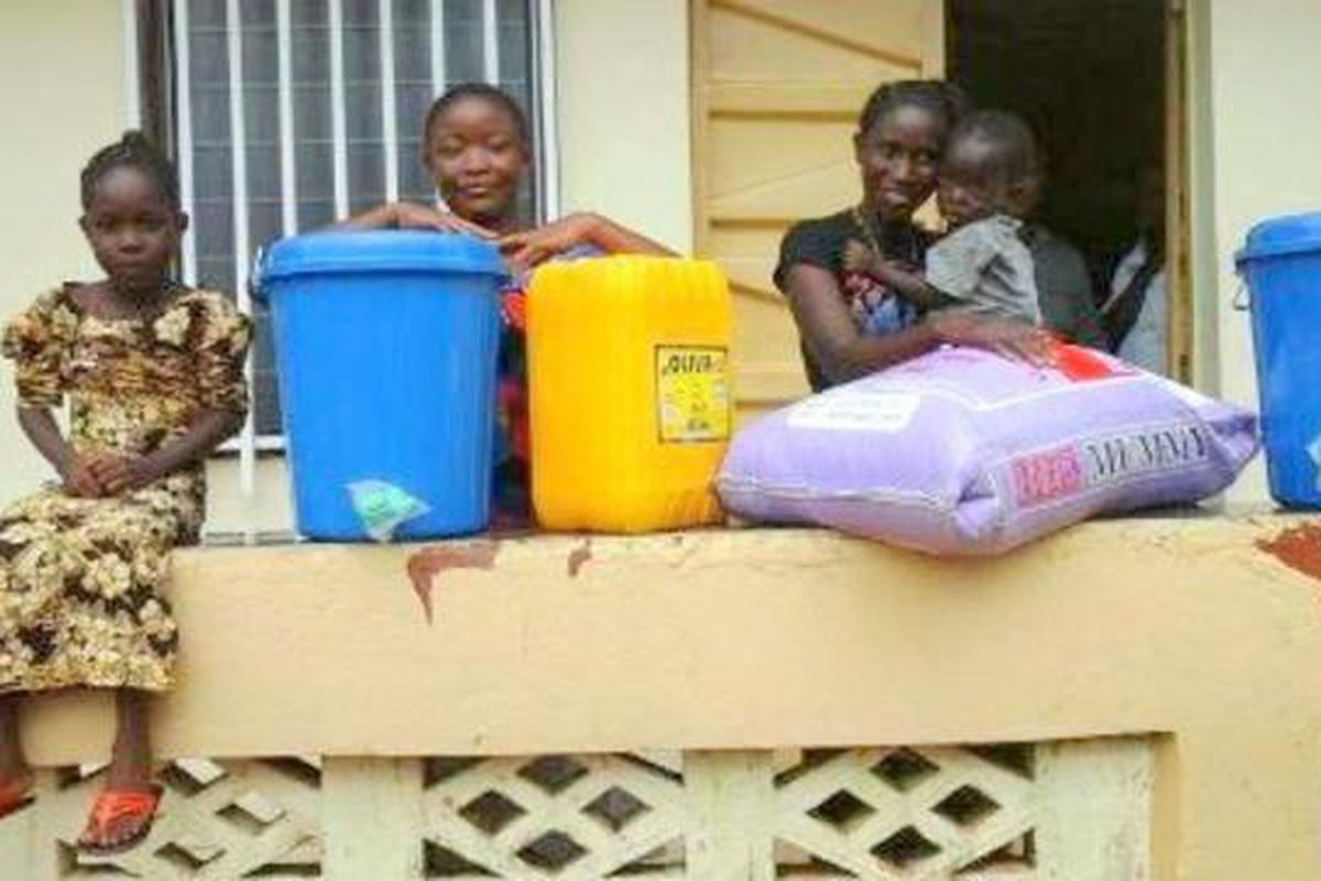A Latter-day Saint family stand next to food and supplies delivered by LDS Charities during Ebola-virus outbreak.