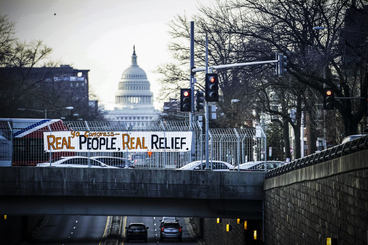 "A banner reading ""Yo Congress - Real People, Real Relief"" is displayed over North Capitol Street near the US Capitol in Washington, DC, on February 26."