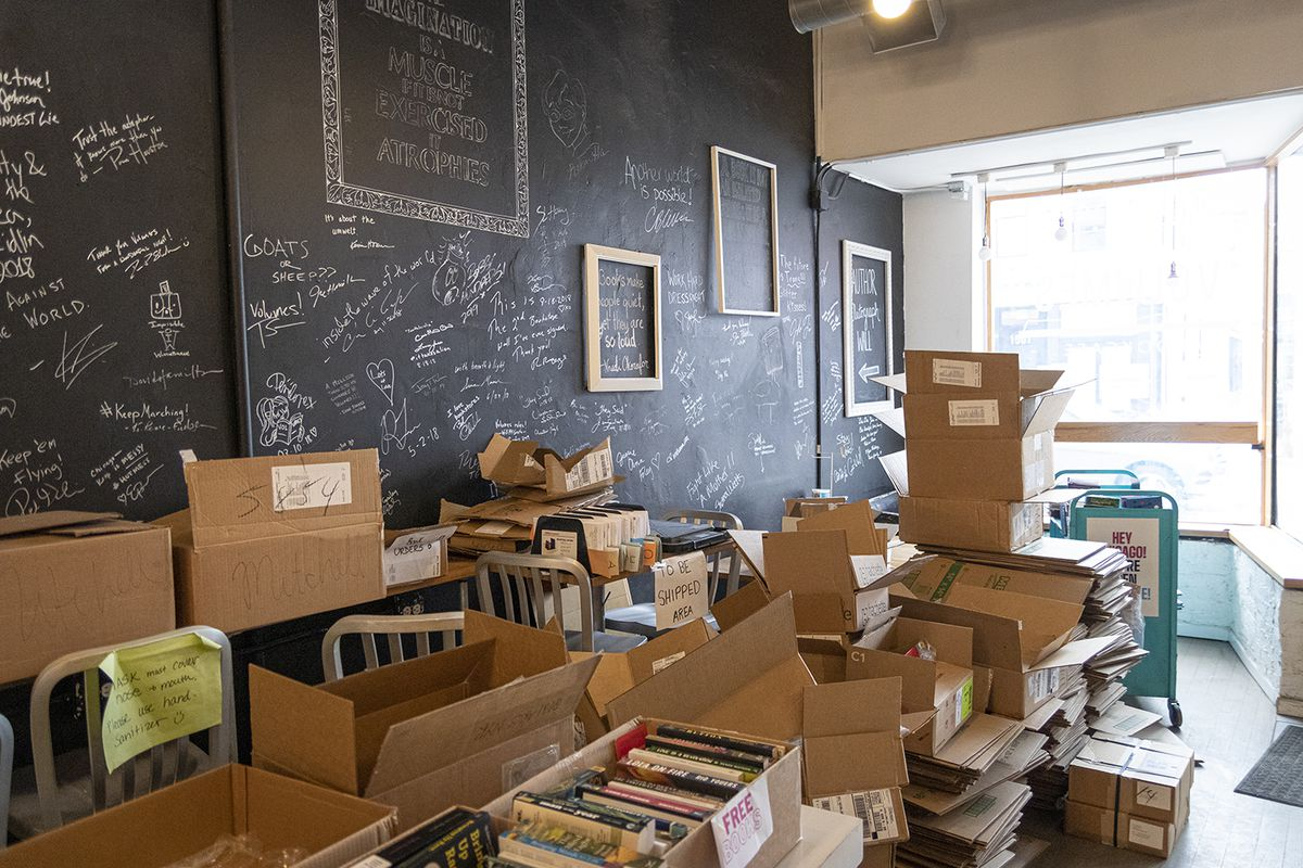 Storage boxes and free book giveaways are piled up near a wall in Volume Bookcafe on Friday, March 26, 2021. The wall is filled with signatures from artists, authors and other celebrity visitors. The store's last day is Saturday.