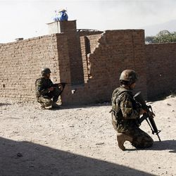 Afghan soldiers provide security after a suicide attack on the U.S.-led provincial reconstruction team (PRT) compound in the Behsood district of Jalalabad, east of Kabul Afghanistan, on Sunday, April 15, 15 2012. The Taliban launched a series of coordinated attacks on at least seven sites across the Afghan capital on Sunday, targeting NATO headquarters, the parliament and diplomatic residences. Militants also launched near-simultaneous assaults in three other eastern cities. (AP Phot/Rahmat Gul)