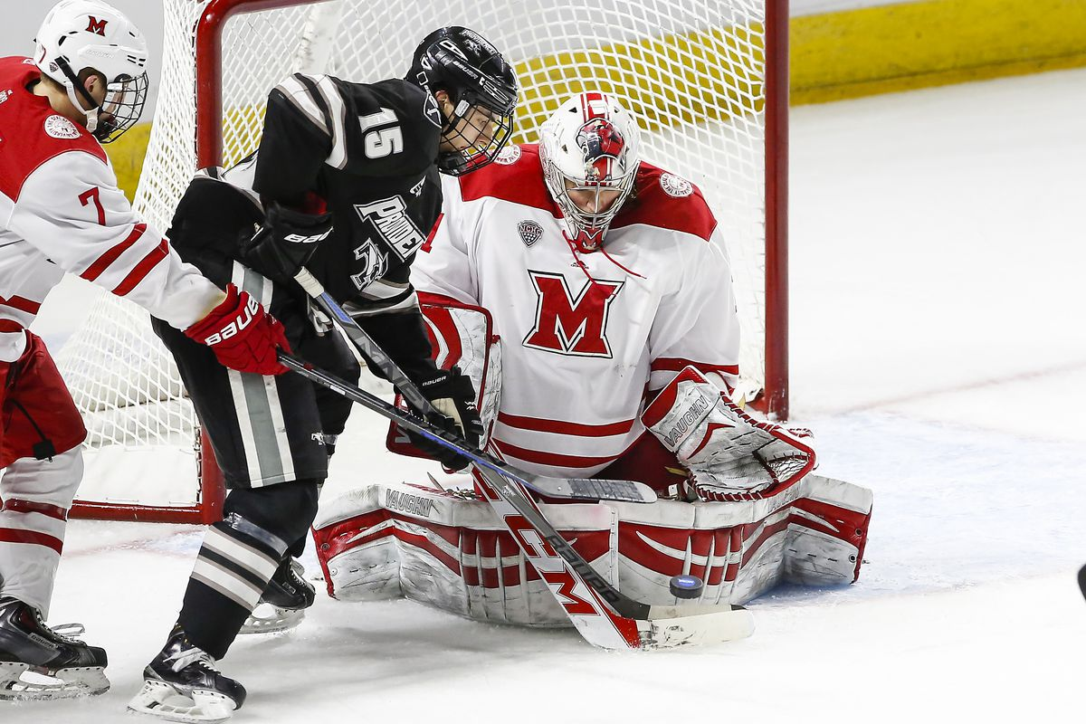 Steven McPartland (Providence #15) tips a puck in front of goaltender Jay Williams (Miami-#1).