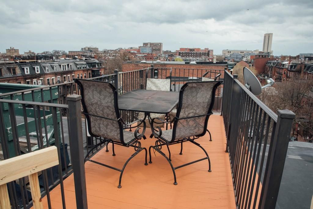 A narrow roof deck with a table and chairs.