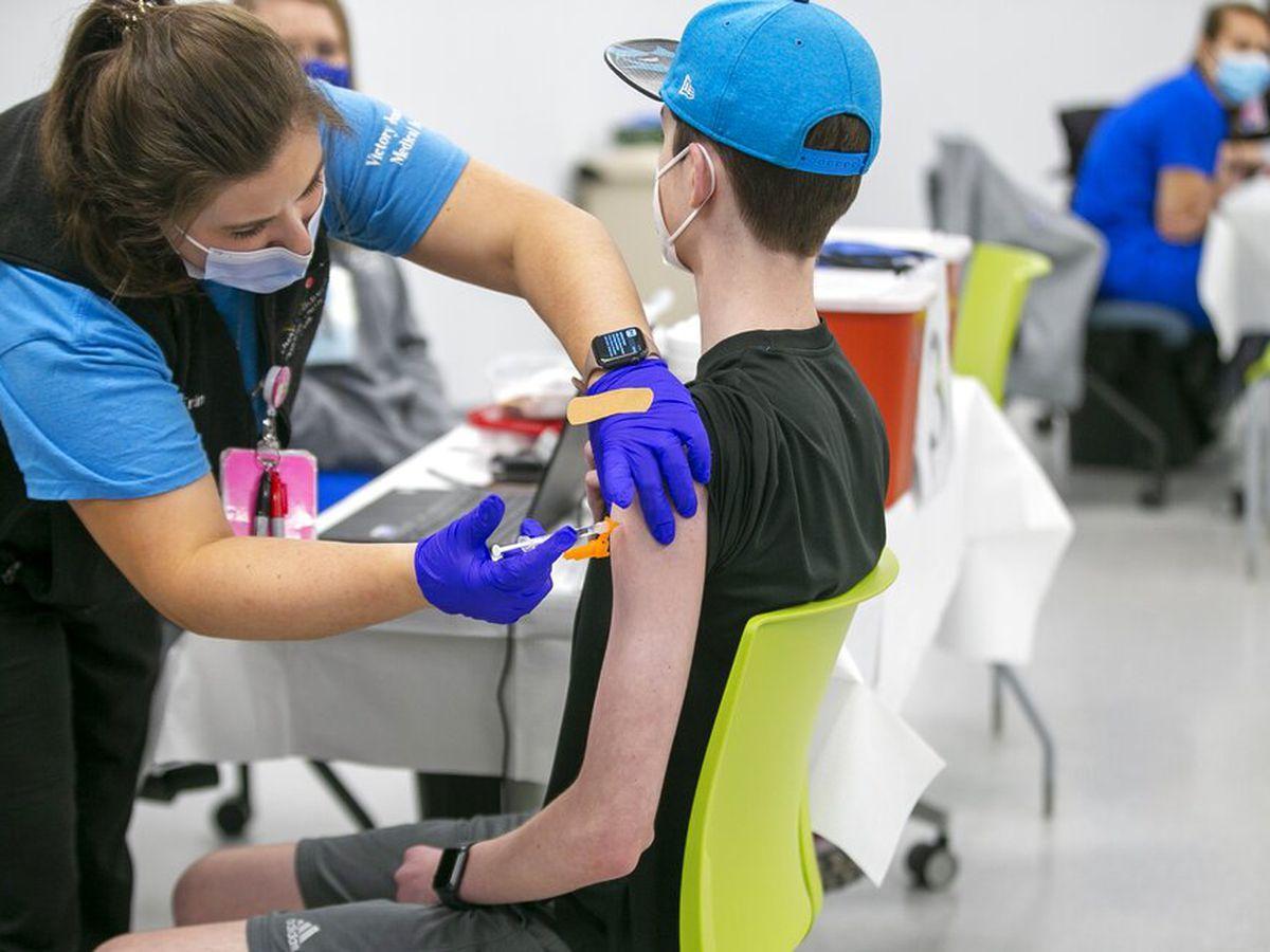 Nurse Erin Morgan administers the Pfizer COVID-19 vaccine to 14-year-old Zach Bilyj.