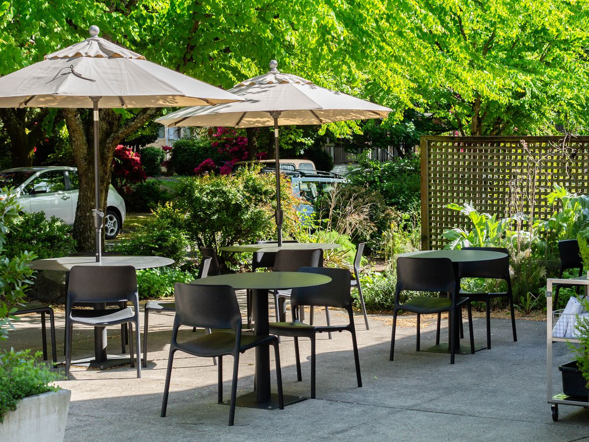 Patio tables with beige umbrellas sit on a small stone courtyard surrounded by green ferns and trees