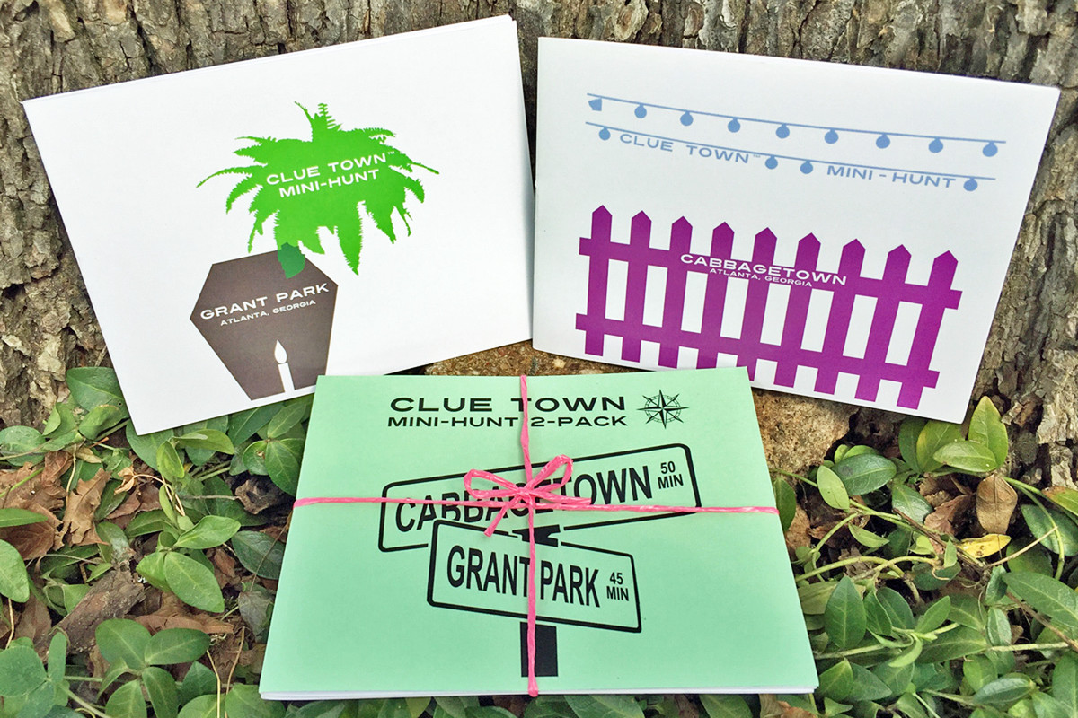 Three cards sit against a tree on a ground covered in foliage. Each card has words on it that read: Clue Town Mini Hunt.