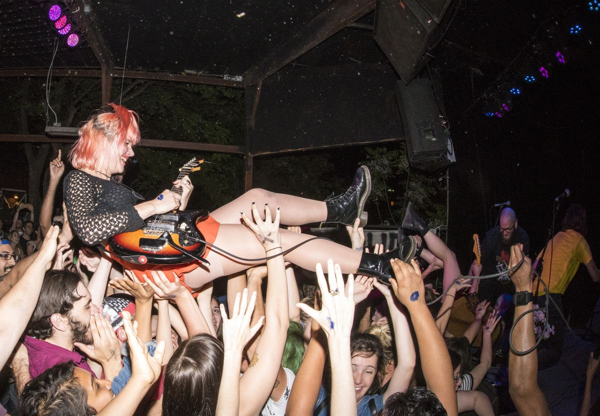 Band frontwoman Jennifer, surfing the crowd while playing guitar.