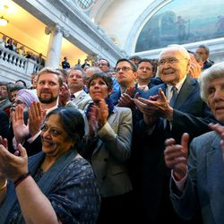 Elder L. Tom Perry, a member of the Quorum of the Twelve Apostles of The Church of Jesus Christ of Latter-day Saints, right, joins equal rights activists, clergy, and others in a round of applause after Gov. Gary Herbert signed SB296 at the Capitol in Salt Lake City on Thursday, March 12, 2015.