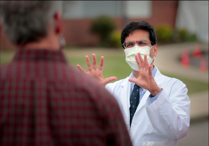 Manoj Jain wears a mask as he talks to Gov. Bill Lee