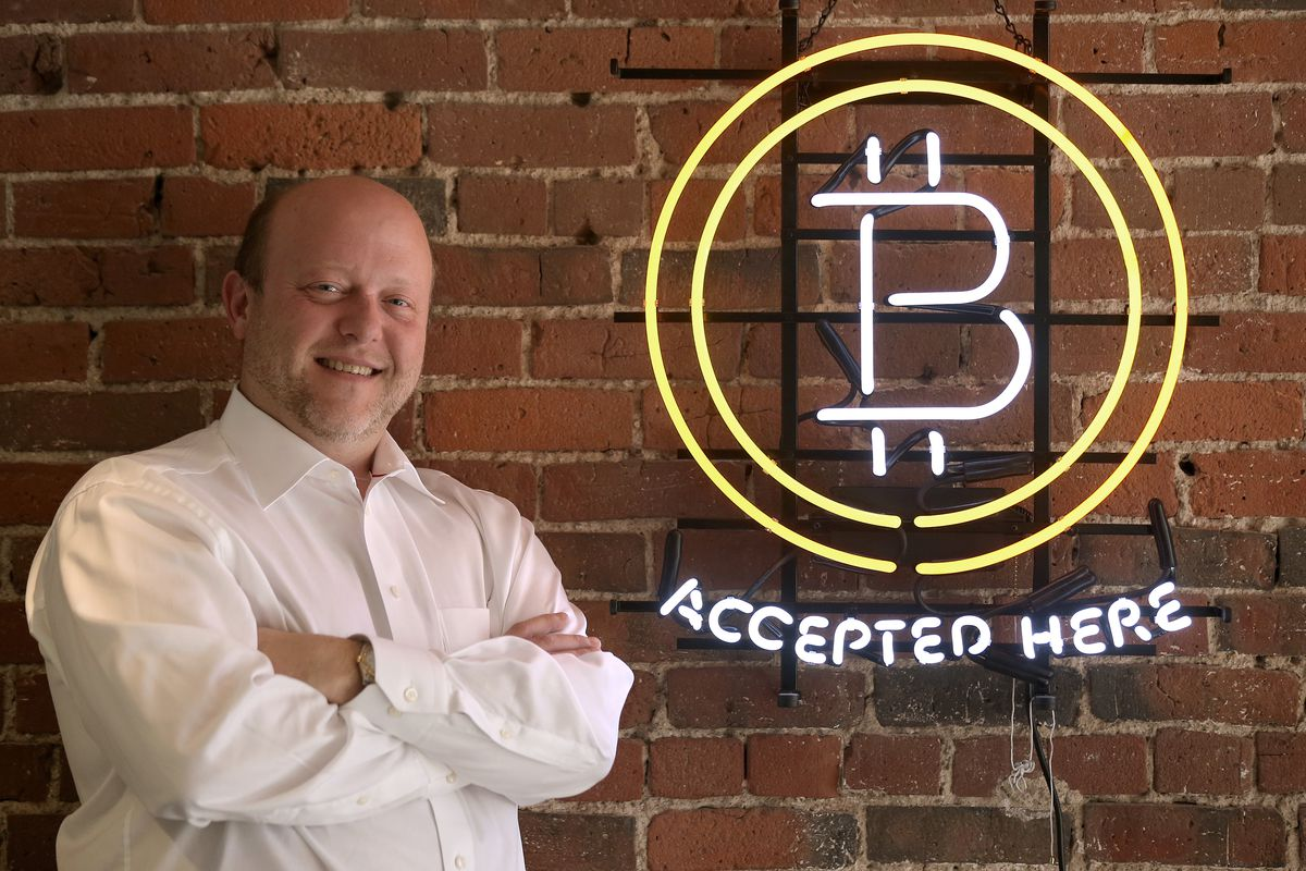 """Circle CEO Jeremy Allaire stands next to a neon sign that reads """"bitcoin accepted here."""""""