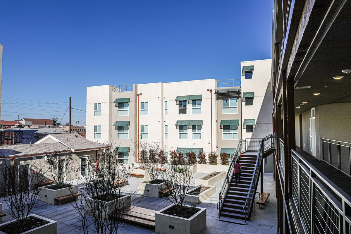 A view from the balcony of an apartment complex looking into a courtyard with tress and planter boxes.
