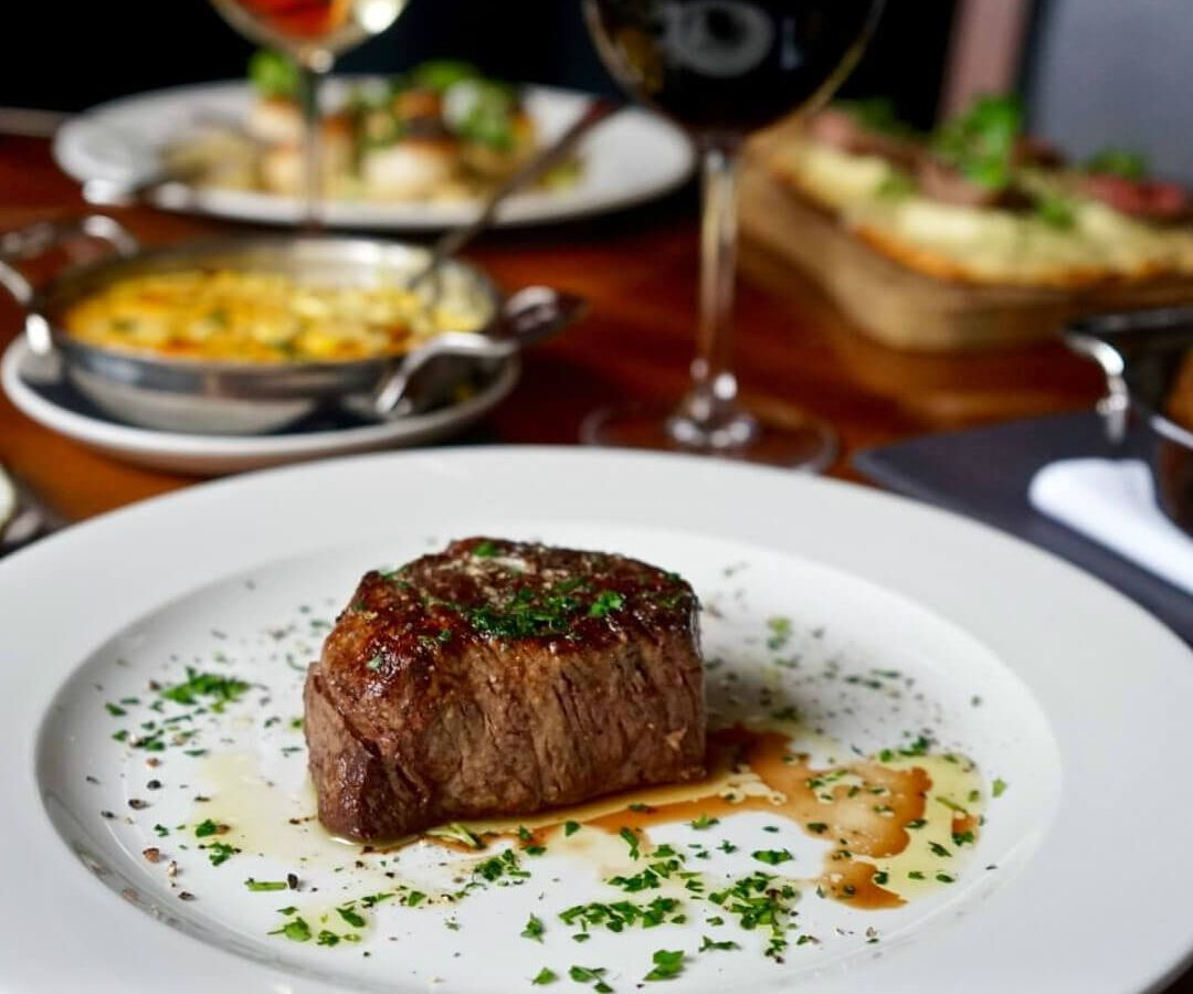 Steak sits alone on a plate at Strip by Strega, with parsley garnish. There are wine glasses and side dishes in the background.