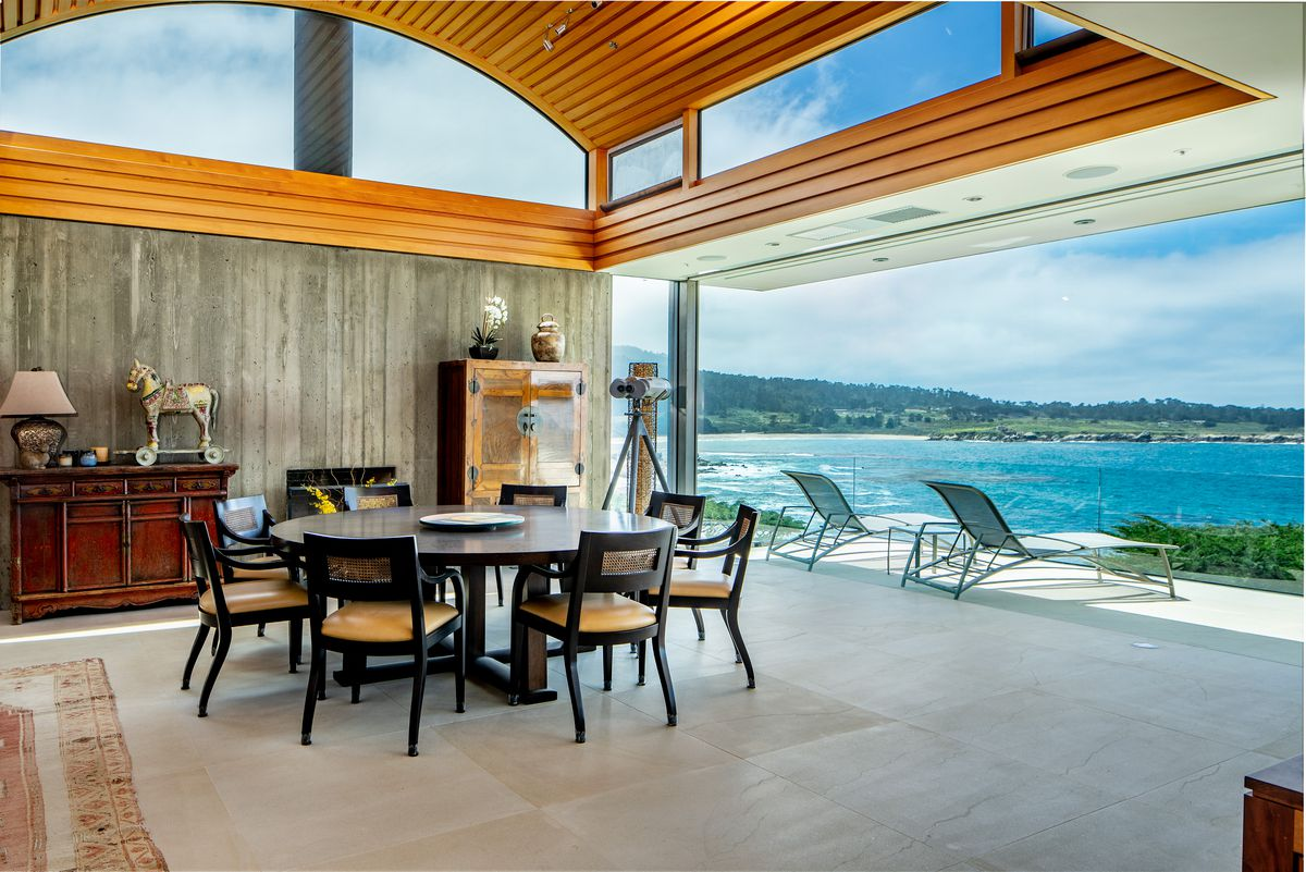 A living room has concrete floors, a round dining room with chairs, and lounge chairs on a patio.