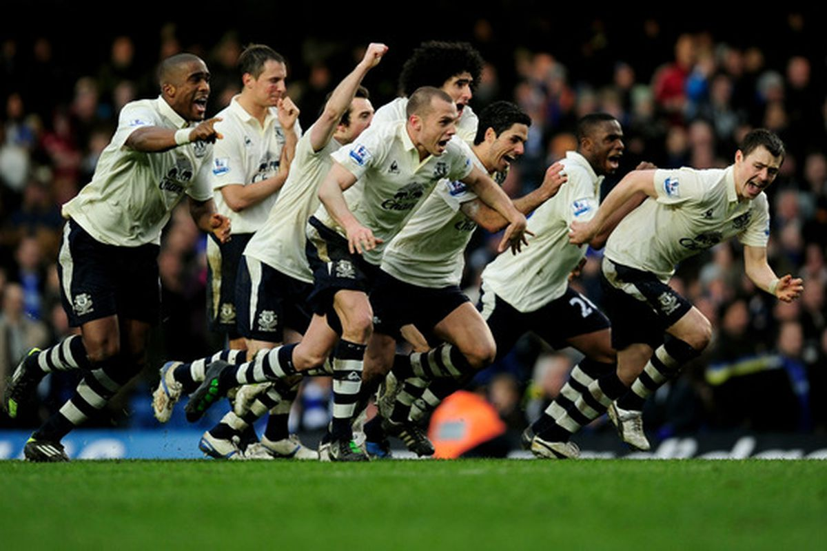 The boys charge Phil Neville after his game winning penalty.