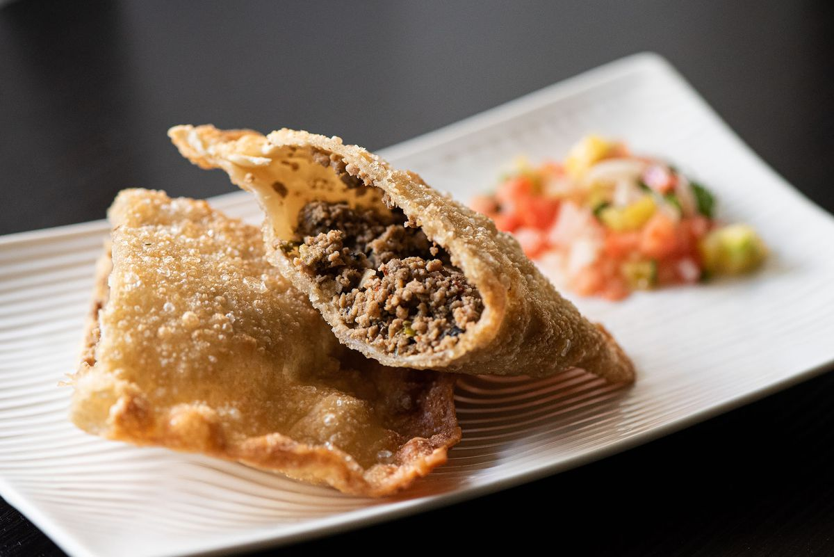 Brazilian fried pasties with meat filling on a white plate.