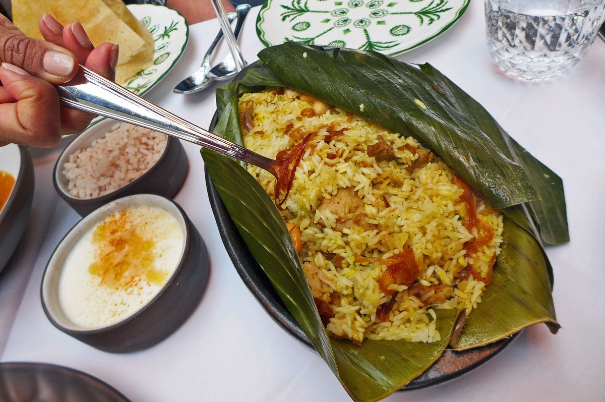 A hand with a spoon reaches into an open deep green leaf cradling a serving of rice casserole.