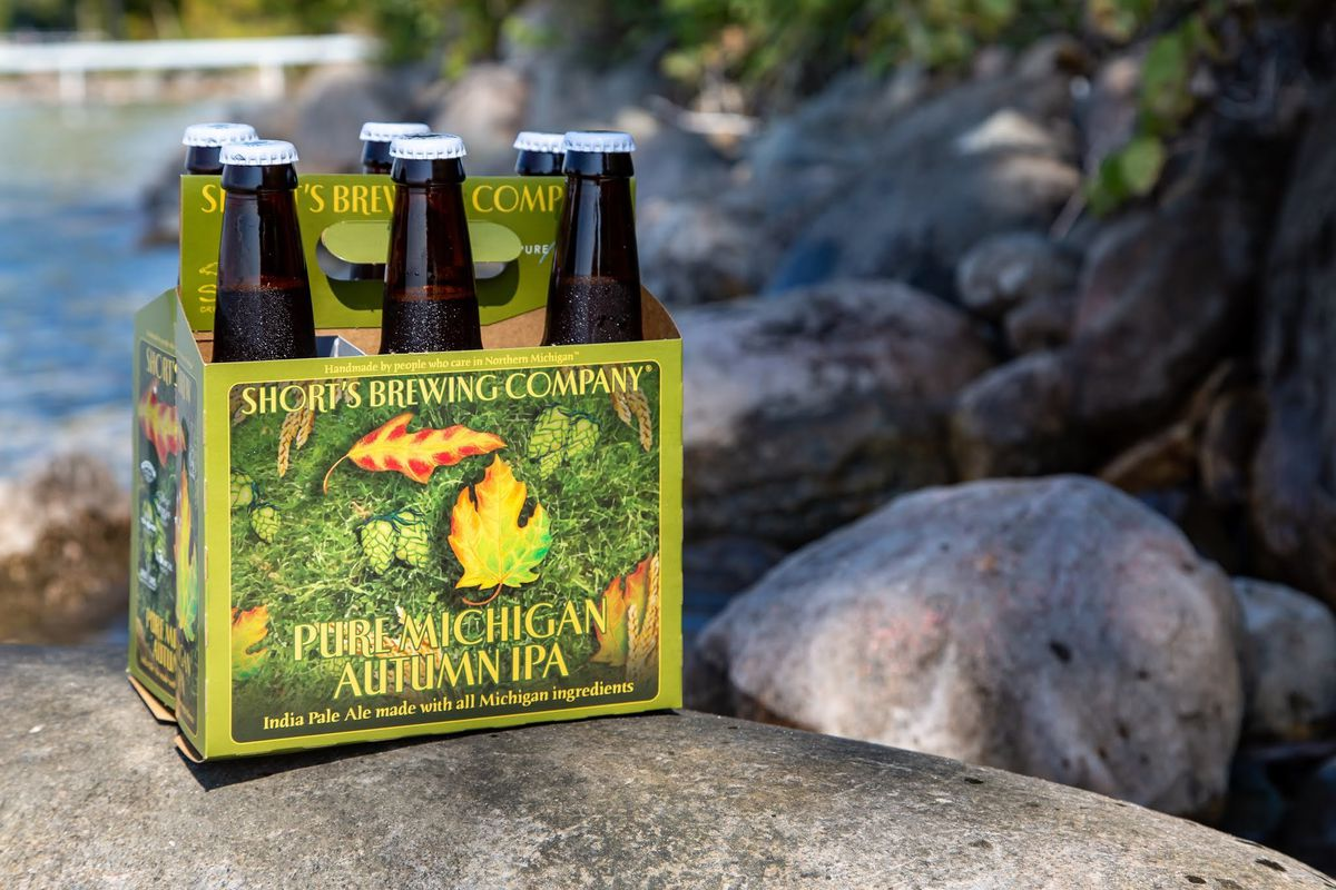 A a Short's-banded six pack of bottled beer in with a green, orange, and yellow illustration of Michigan with the Upper Peninsula shaped like a leaf.