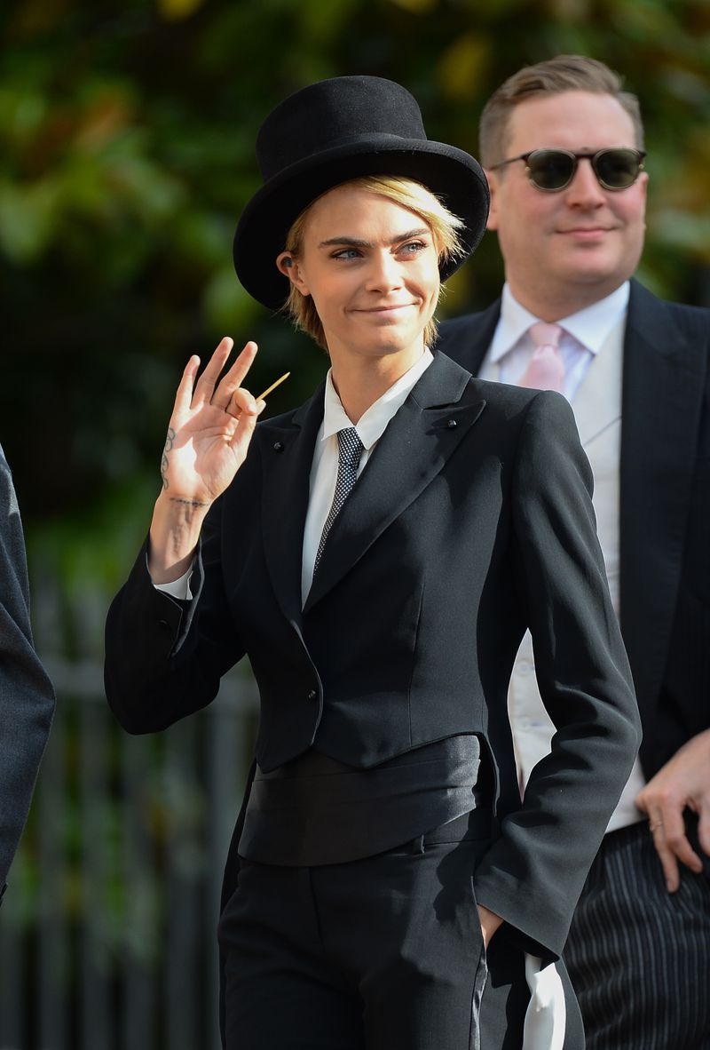 Cara Delevingne waves to someone, toothpick in hand.