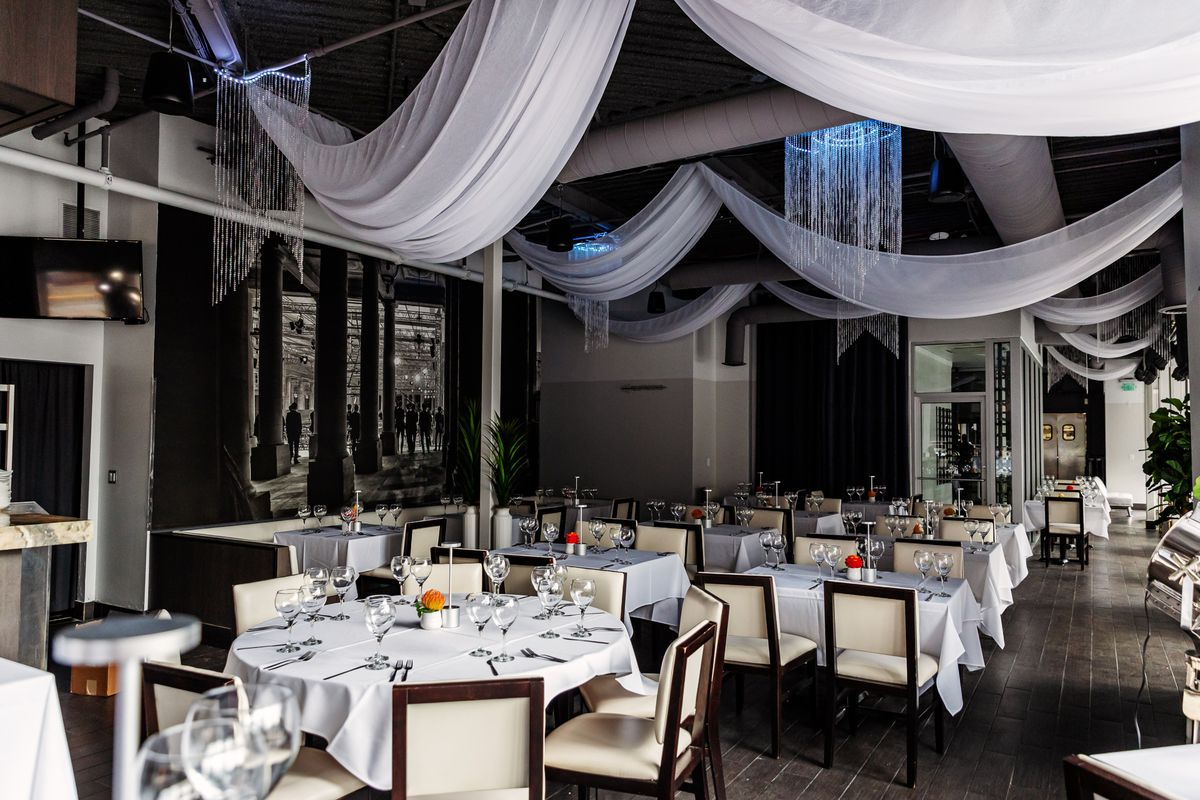 A restaurant dining room full of white tables and chairs