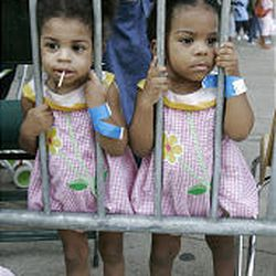 Starr Toca, left, and her sister, Skye Toca, 19-month-old twin evacuees from New Orleans, stand behind a barricade at Reunion Arena in Dallas.