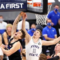 Brigham Young Cougars center Richard Harward (42) flips the ball up and in over Weber State Wildcats forward Michal Kozak (11) as BYU and Weber State play an NCAA basketball game at Vivint Smart Home Arena in Salt Lake City on Wednesday, Dec. 23, 2020. BYU won 87-79.