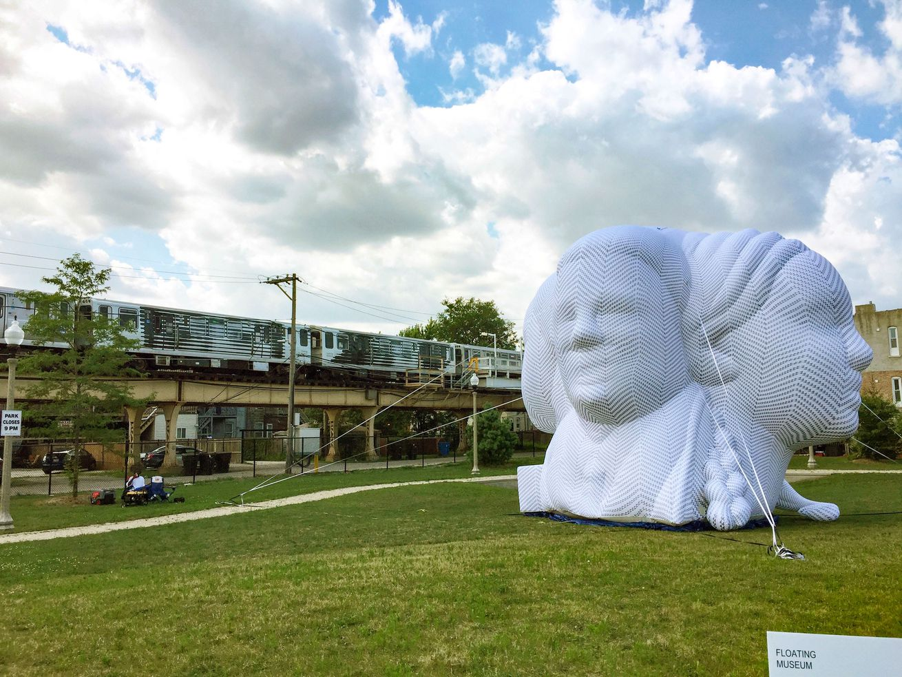 On a grassy lawn an inflated, 25-foot, four-faced bust sits next to rusty, yellow elevated train tracks in Chicago under a blue and puffy cloudy sky.