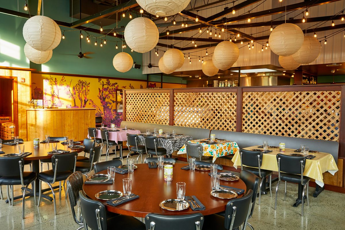 A restaurant dining room with big round wooden tables in the center of the room and rectangular tables covered in oilcloth table cloths, one in pink houndstooth, one zebra, and one in an orange fruit pattern
