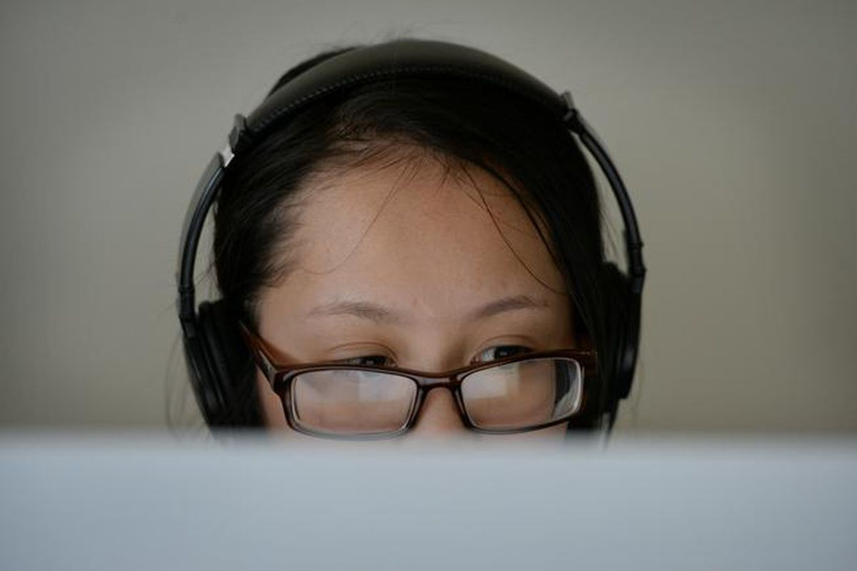 A sixth-grade student wearing headphones apears to look at a computer screen while taking a test.