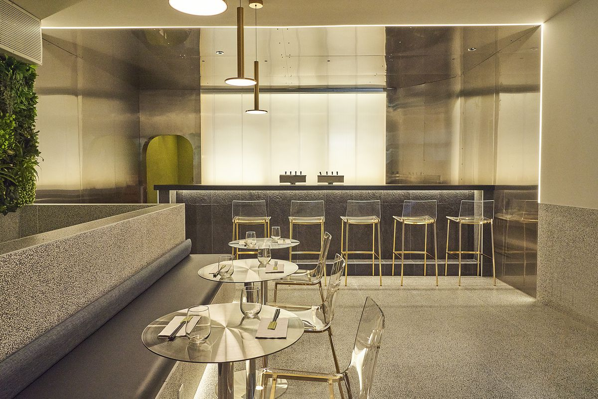 A warm, yellow-lit space with leather banquettes and a counter in the background with high-top seating.