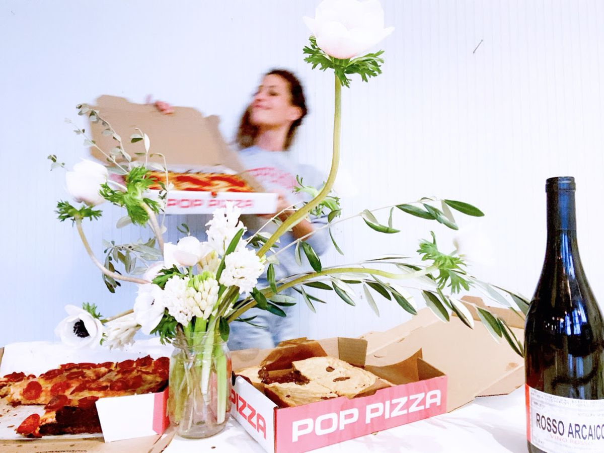 In the foreground, two pizza boxes rest on a white table next to a bottle of wine and a vase of long stemmed white flowers. A woman with an open pizza box is out of focus in the background.