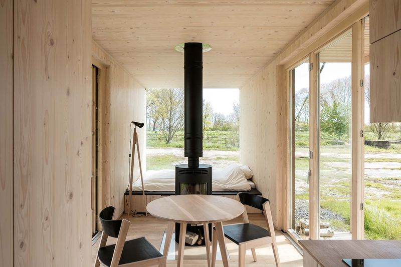 the homes facade is painted a trendy black on the outside with pale wood paneling within the interior foregoes the typical tiny house bedroom loft in - Prefab Tiny House