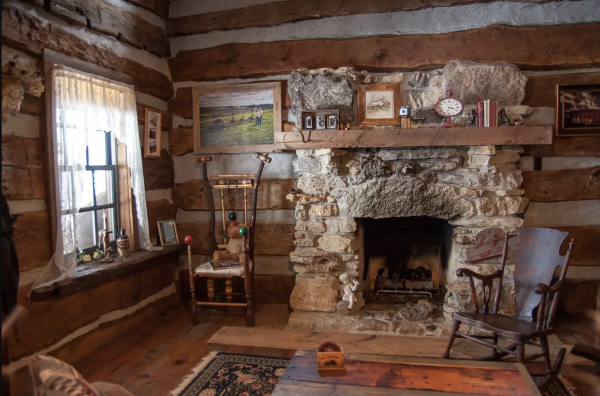 A rough stone fireplace with a wood mantel. There are two wooden rocking chairs and a window with sheer drapes.