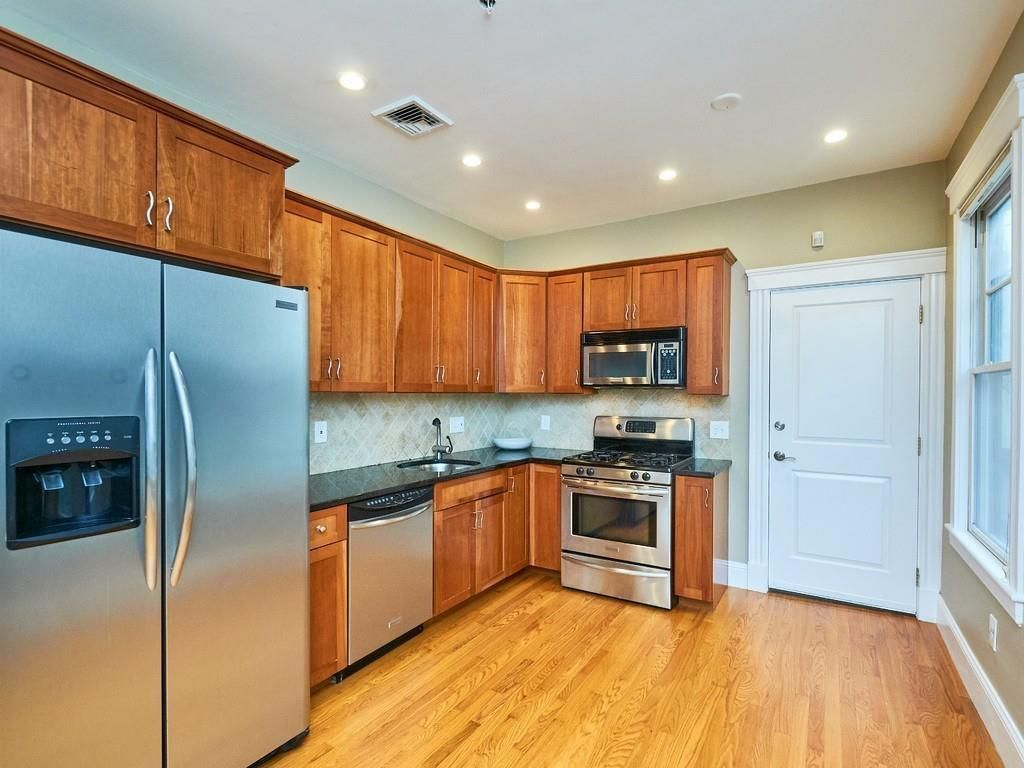 A corner kitchen area with an L-shaped counter and a closed pantry door.