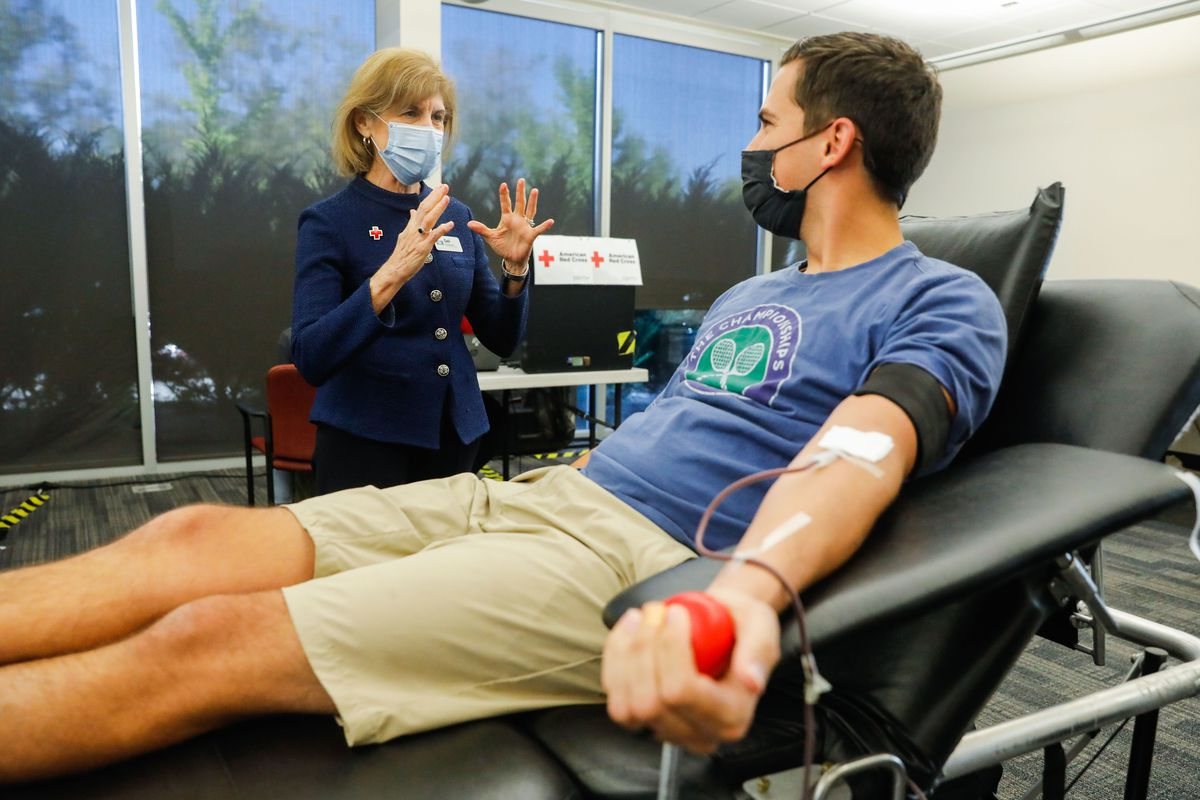 American Red Cross President and CEO Gail McGovern talks to BYU student while he donates blood on the Provo, Utah, campus.