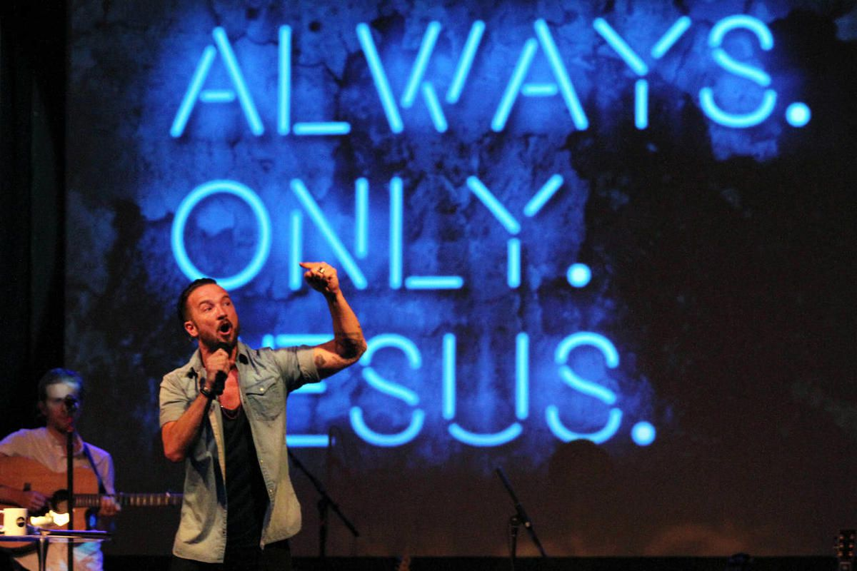 In this July 14, 2013 photo, Pastor Carl Lentz, foreground, leads a Hillsong NYC Church service at Irving Plaza in New York. With his half-shaved head, jeans and tattoos, Lentz doesn't look like the typical religious leader. But with its concert-like atmo