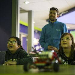 Paloma Velazquez, left, and Emma Hopper, right, watch as their instructor Duncan Humphries shows them how engineering graduate students program robots to play soccer during a Lego Camp at Zaniac Learning in Salt Lake City on Monday, Feb. 20, 2017.