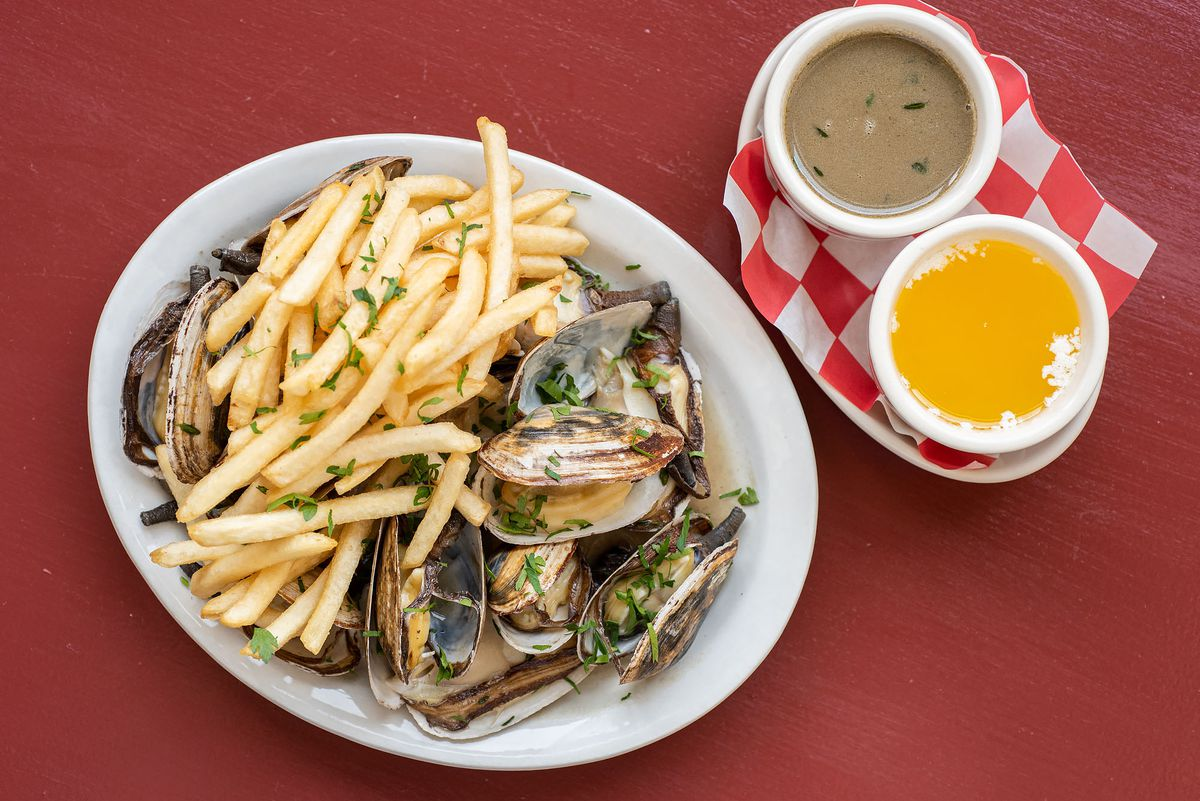 Steamer clams with fries and sauces to the side.