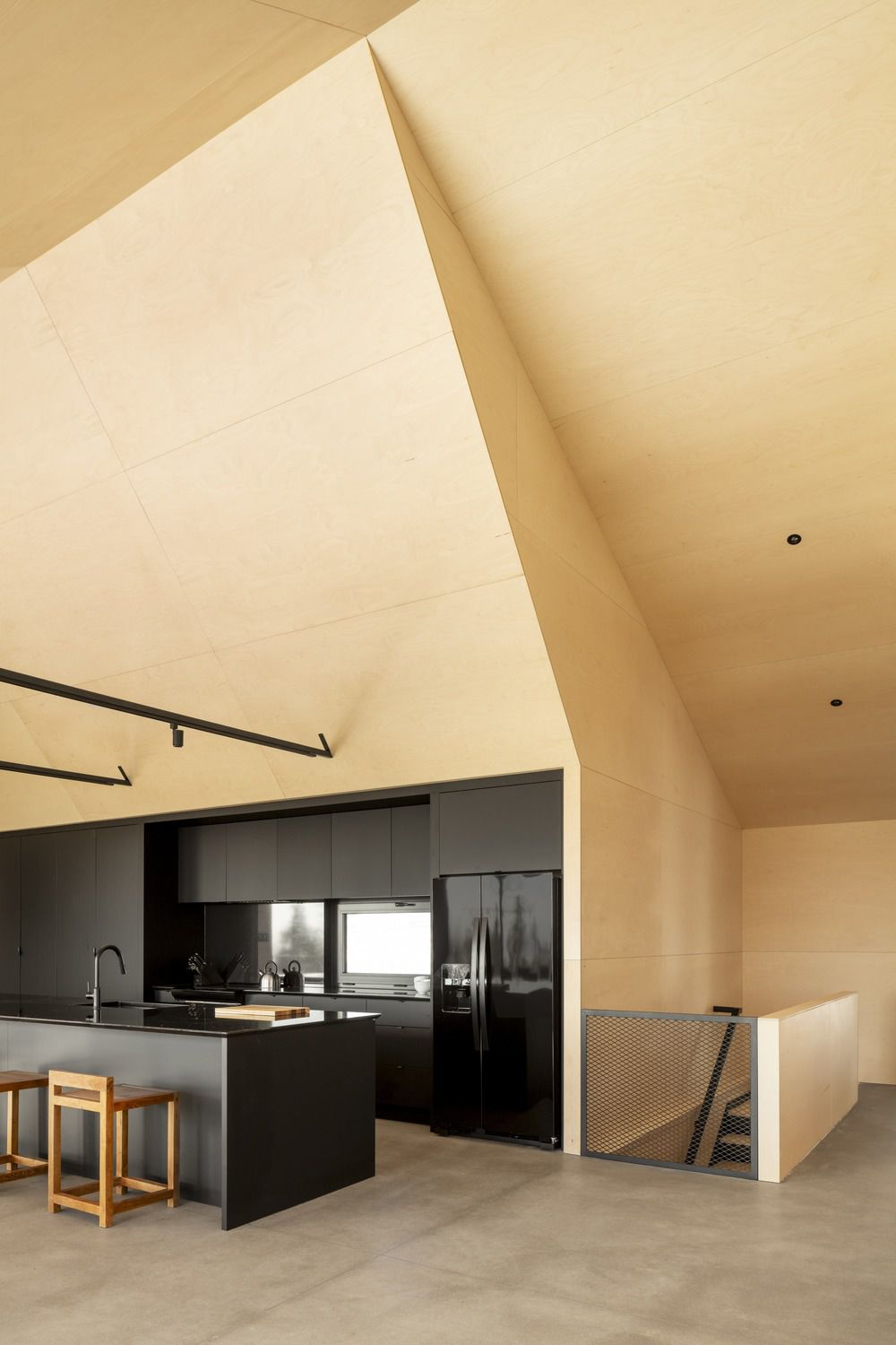 Black cabinets and plywood in kitchen under soaring angular ceilings.