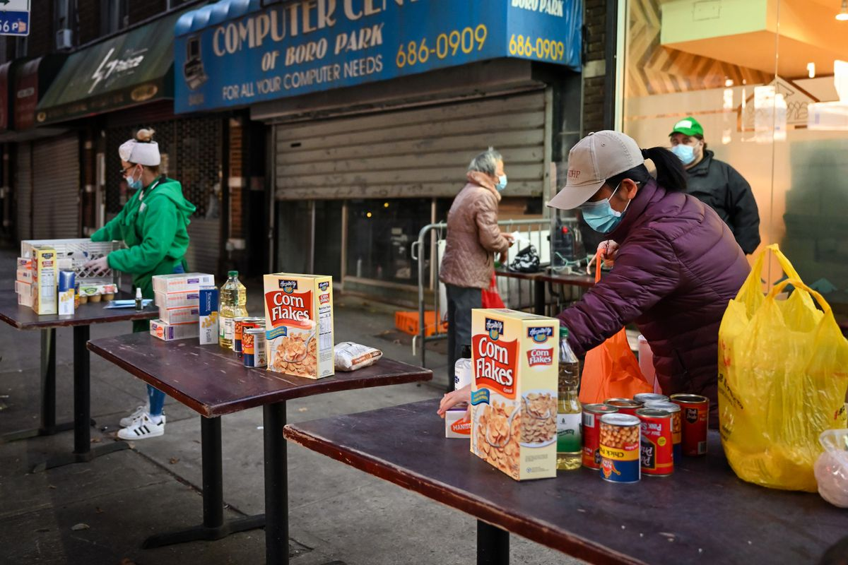 Masbia employees piled food on three tables outside of the Borough Park pantry while people picked up food early in the morning ahead of Thanksgiving.