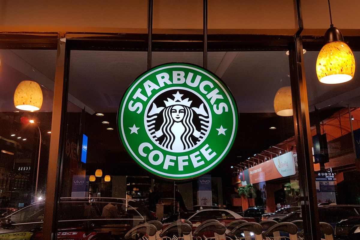 """A """"Starbucks Coffee"""" sign hanging in front of a window."""
