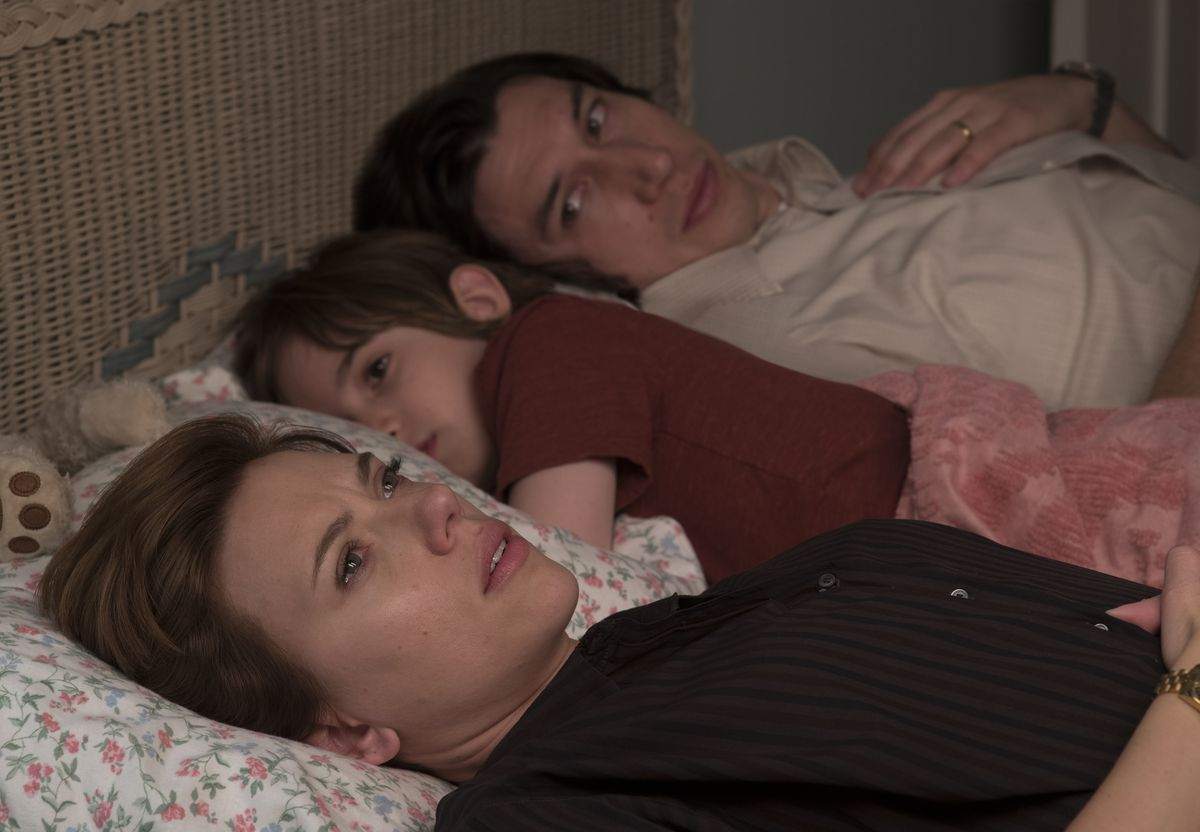 Two adults lay on a bed with their child snuggled between them.