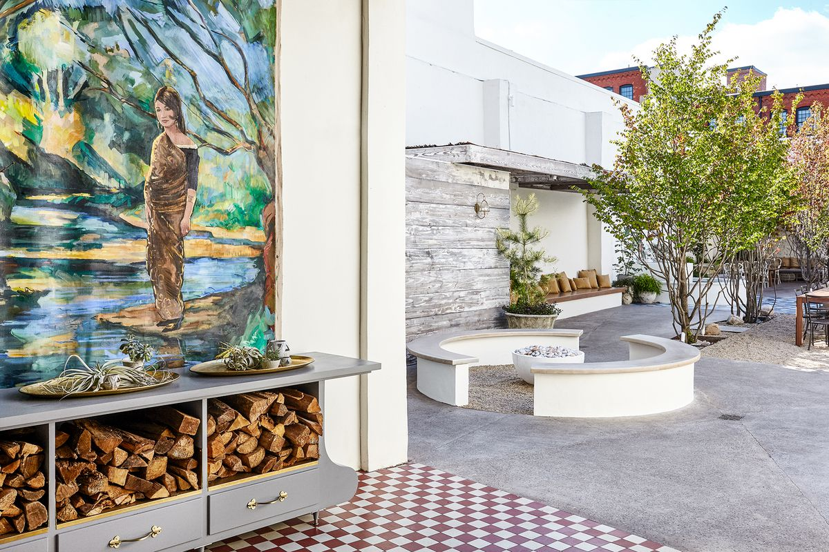 outdoor area with mural of woman, firepit, stacked wood, and trees
