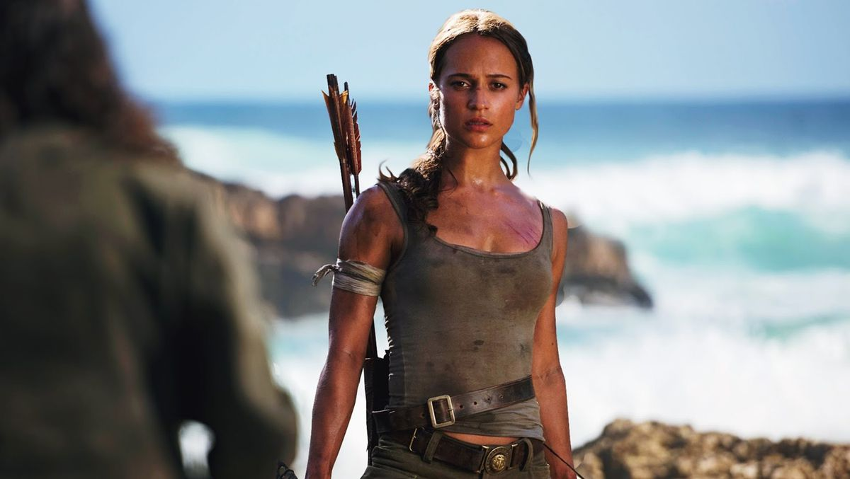 Alicia Vikander as Lara Croft in a tank top and standing in front of the sea carrying a bow in the 2018 Tomb Raider movie