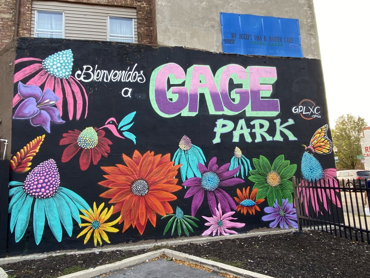 """This mural by Mario Mena — head of the Gage Park Mural Project — includes flowers, a butterfly and the welcoming words """"Bienvenidos a Gage Park."""""""