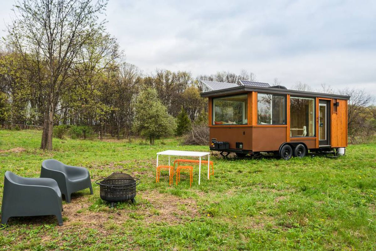 A tiny house with wooden siding and large windows sits in the middle of a field, with tables and chairs close by.