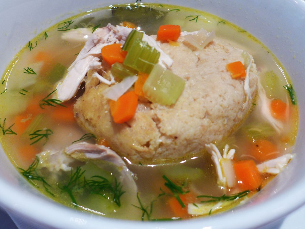A large ball of matzah sits in broth, topped with celery, carrot, chicken, and dill