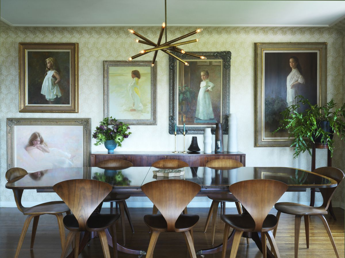 Chairs with ginkgo leaf-shaped backs surround a vintage table. Paintings of a girl hang on a wall in the background.